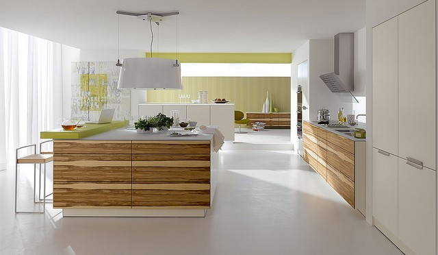 open white kitchen with wooden draws on counter cupboards and a lime green back wall